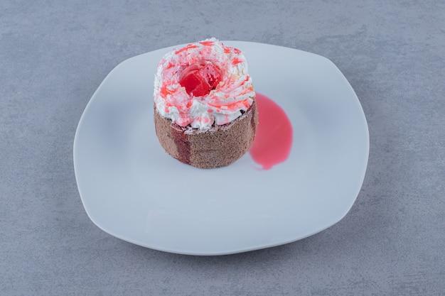 Selbst gemachter cremiger minikuchen mit rosa soße auf weißem teller