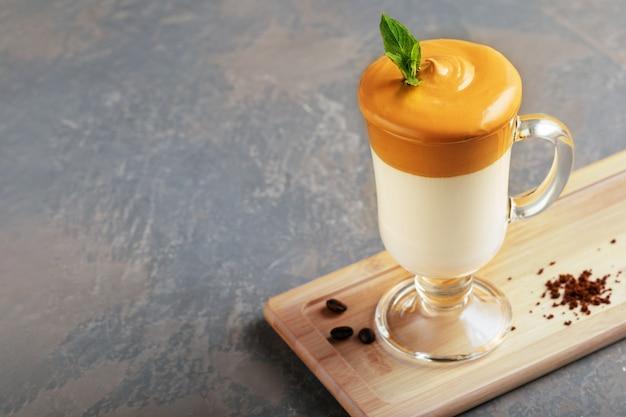 Selbst gemachter dalgona-kaffee in der glasschale auf holzbrett auf grauem hintergrund. trend koreanisches iced latte kaffeegetränk mit schaum von instantkaffee mit kaffeebohnen.