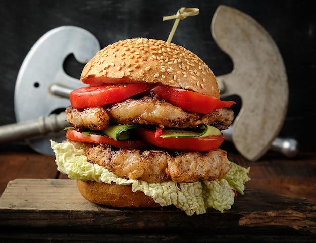 Selbst gemachter doppelter hamburger mit schweinefleisch briet steak, rote tomaten, frisches rundes brötchen