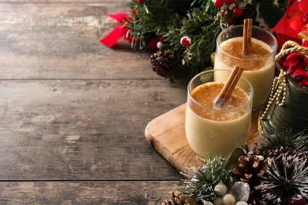 Selbst gemachter eierpunsch mit zimt im glas auf holztisch, typischer weihnachtsnachtisch.
