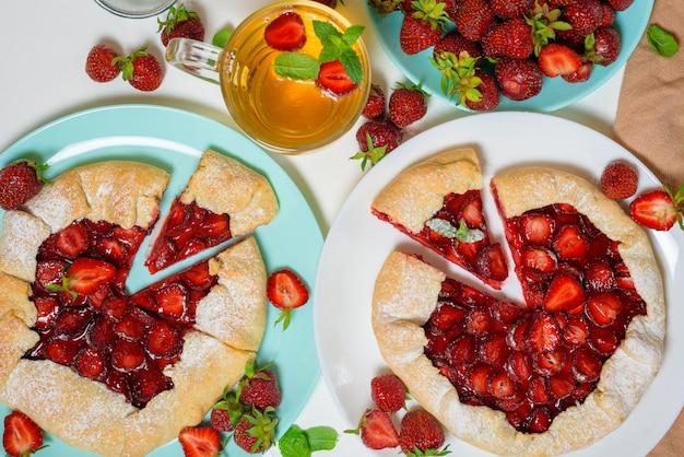 Selbst gemachter erdbeerkeks mit frischen reifen erdbeeren auf blauen und weißen tellern mit tee auf hellem hintergrund, draufsicht