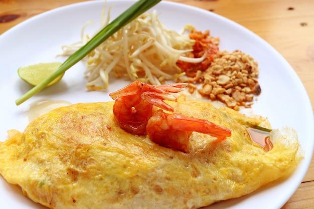 Selbst gemachter fried egg wrapped pad thai noodle mit den garnelen gedient auf weißer platte