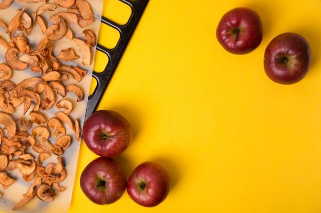 Selbst gemachter getrockneter bio-apfel geschnitten auf gelbem tisch.
