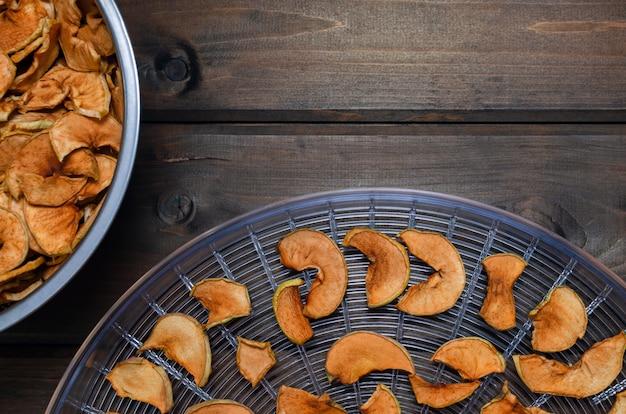 Selbst gemachter getrockneter organischer apfel geschnitten auf hölzerner tabelle.