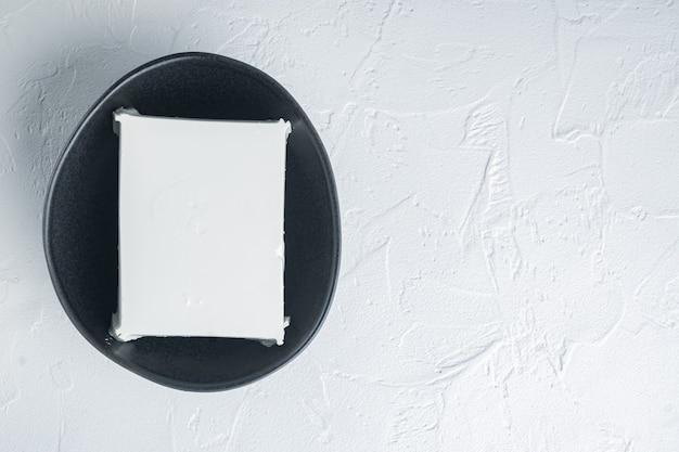 Selbst gemachter griechischer käse-feta-satz, auf weißem hintergrund, flach lag mit kopienraum für text