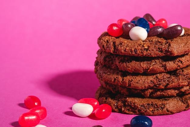 Selbst gemachter haferschokoladenplätzchenstapel mit getreide mit saftigen gummibärchen auf minimalem rosa lila hintergrund, winkelansicht-makro