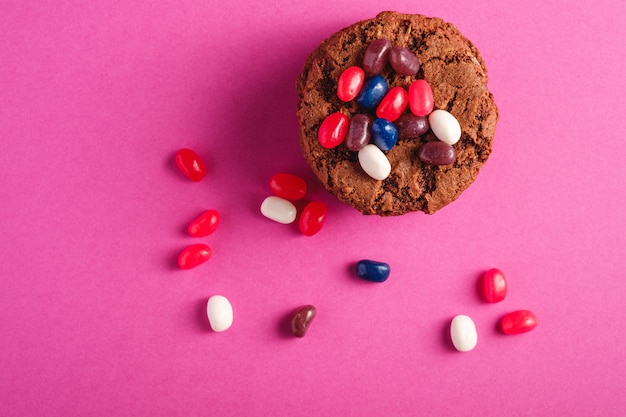 Selbst gemachter haferschokoladenplätzchenstapel mit müsli mit saftigen gummibärchen auf minimalem rosa lila hintergrund, draufsicht
