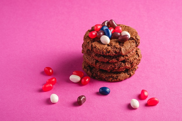 Selbst gemachter haferschokoladenplätzchenstapel mit müsli mit saftigen gummibärchen auf minimaler rosa lila oberfläche, winkelansicht