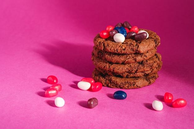 Selbst gemachter haferschokoladenplätzchenstapel mit müsli mit saftigen gummibärchen auf minimaler rosa lila wand, winkelansicht