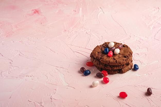 Selbst gemachter haferschokoladenplätzchenstapel mit müsli mit saftigen gummibärchen auf strukturiertem rosa hintergrund, blickwinkelkopienraum