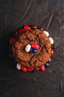 Selbst gemachter haferschokoladenplätzchenstapel mit müsli mit saftigen gummibärchen auf strukturierter dunkelschwarzer oberfläche, draufsicht