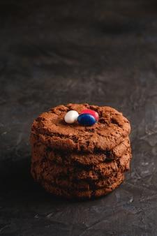Selbst gemachter haferschokoladenplätzchenstapel mit müsli mit saftigen gummibärchen auf strukturierter dunkler schwarzer oberfläche, winkelansicht