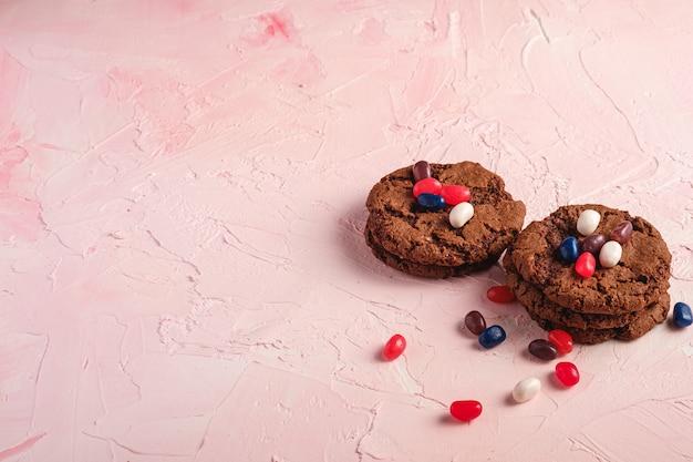 Selbst gemachter haferschokoladenplätzchenstapel mit müsli mit saftigen gummibärchen auf strukturierter rosa oberfläche, winkelansicht kopienraum