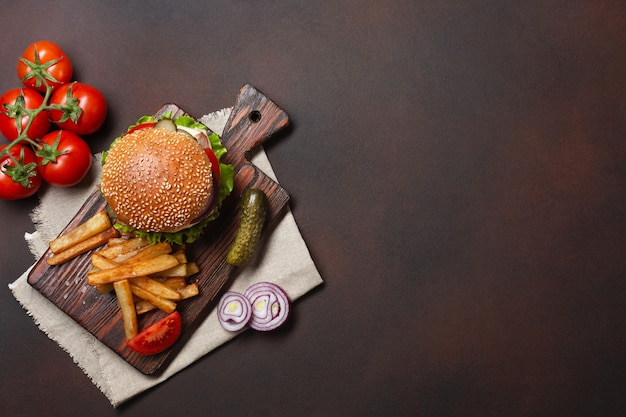 Selbst gemachter hamburger mit bestandteilen rindfleisch, tomaten, kopfsalat, käse, zwiebel, gurken und pommes-frites auf schneidebrett