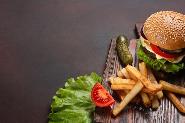 Selbst gemachter hamburger mit bestandteilen rindfleisch, tomaten, kopfsalat, käse, zwiebel, gurken und pommes-frites