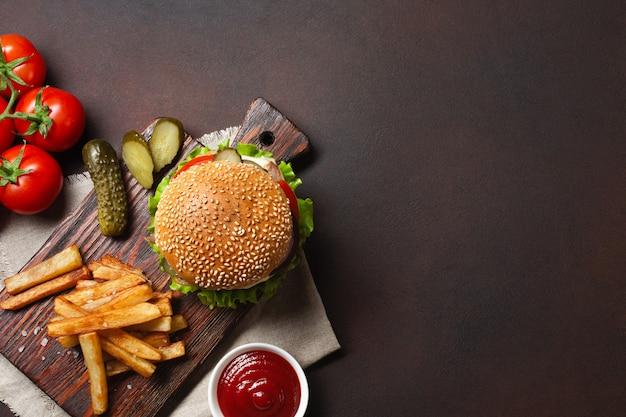 Selbst gemachter hamburger mit bestandteilrindfleisch, tomaten, kopfsalat, käse, zwiebel, gurken und pommes-frites auf schneidebrett und rostigem hintergrund