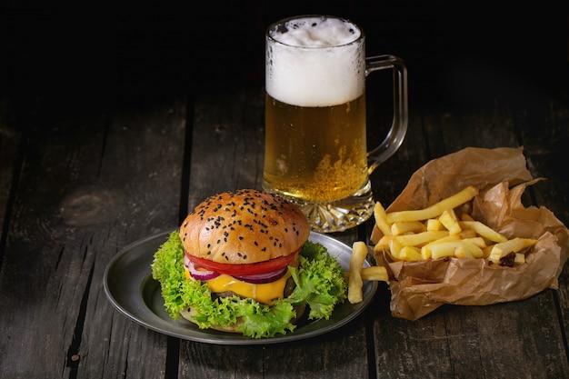 Selbst gemachter hamburger mit bier und kartoffeln