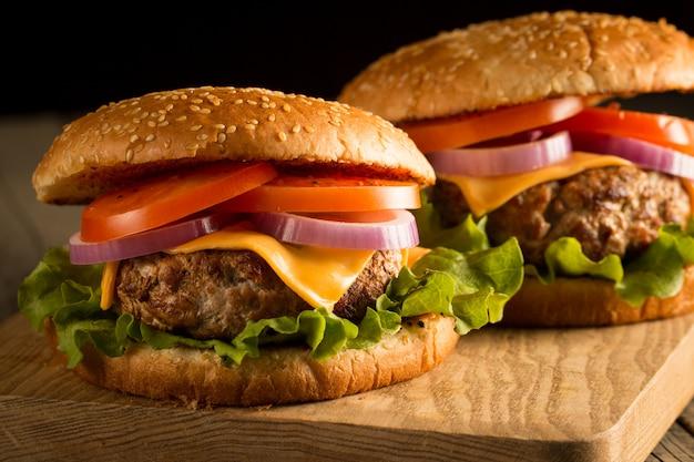 Selbst gemachter hamburger mit rindfleisch, zwiebel, tomate, kopfsalat und käse. frischer burger nah oben auf hölzerner rustikaler tabelle mit kartoffelfischrogen, bier und chips. cheeseburger.