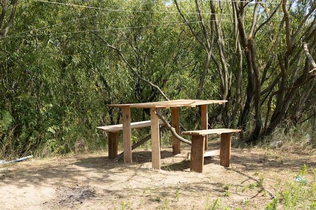 Selbst gemachter holztisch mit stühlen auf einem hintergrund von bäumen.