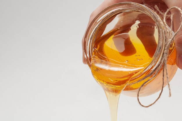 Selbst gemachter honig, der aus glas gießt