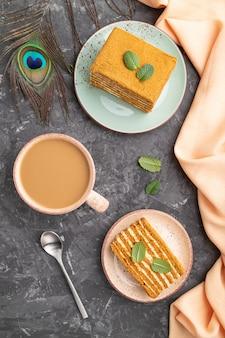 Selbst gemachter honigkuchen mit milchcreme und minze mit tasse kaffee auf einem schwarzen betonhintergrund. draufsicht, nahaufnahme.