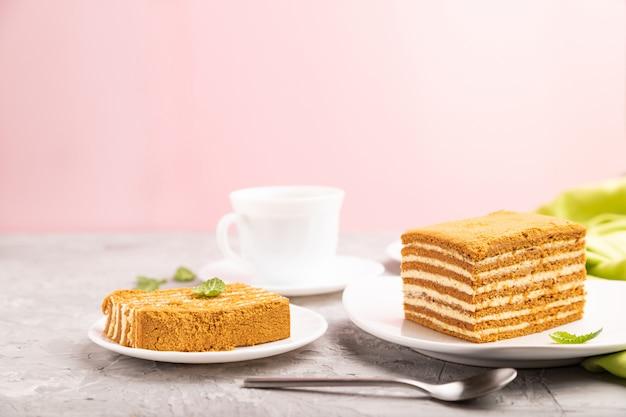 Selbst gemachter honigkuchen mit milchcreme und minze mit tasse kaffee auf einem und rosa hintergrund. seitenansicht,