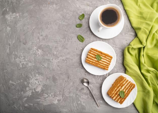 Selbst gemachter honigkuchen mit milchcreme und minze mit tasse kaffee auf grauem betonhintergrund. draufsicht,