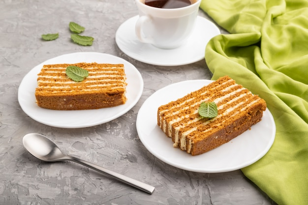 Selbst gemachter honigkuchen mit milchcreme und minze mit tasse kaffee auf grauem betonhintergrund. seitenansicht, nahaufnahme.