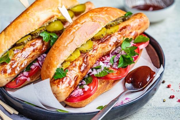 Selbst gemachter hot dog mit wurst, gemüse und würziger soße, grauer hintergrund.