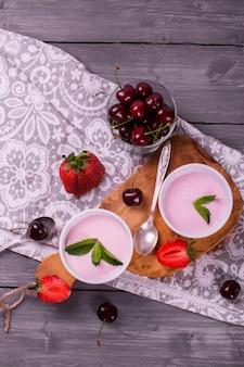 Selbst gemachter joghurt mit frischer erdbeere, süßer kirsche und minze auf hölzernen planken