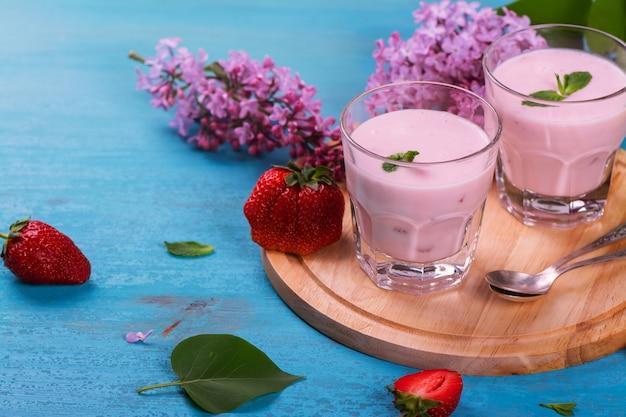 Selbst gemachter jogurt mit frischer erdbeere und minze auf blauem hölzernem hintergrund