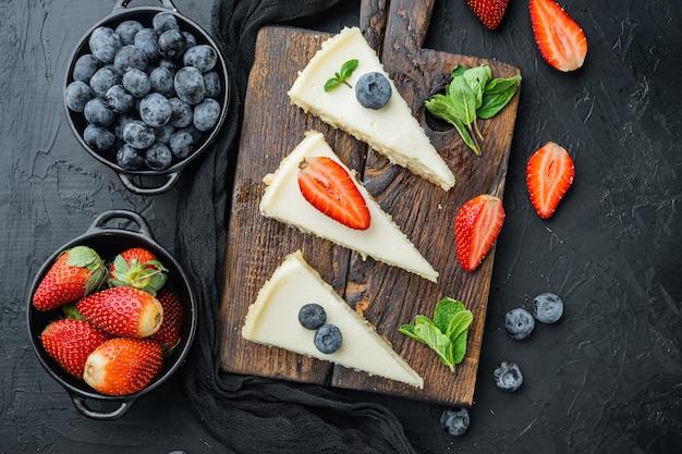 Selbst gemachter käsekuchen mit frischen beeren auf schwarzer draufsicht flache lage