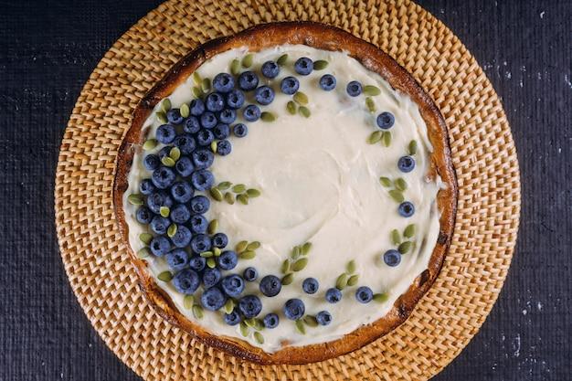 Selbst gemachter käsekuchen mit frischen blaubeeren und kürbiskernen