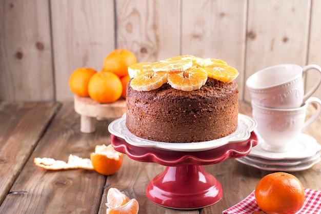 Selbst gemachter kleiner kuchen mit tangerinen auf einer weißen platte