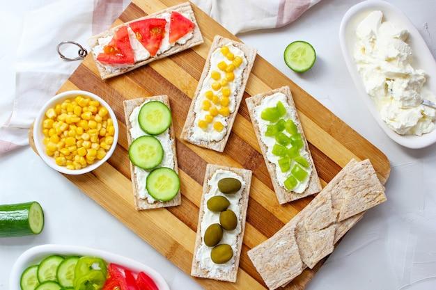 Selbst gemachter knäckebrottoast mit hüttenkäse und grünen oliven, kohlscheiben, tomaten, mais, grünem paprika auf schneidebrett. gesundes lebensmittelkonzept, draufsicht. flache lage