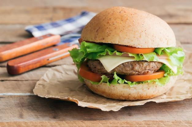 Selbst gemachter köstlicher sandwichhamburger mit fleisch- oder schweinefleischschinkenkäse und frischgemüse.