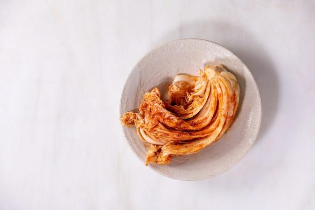 Selbst gemachter koreanischer traditioneller fermentierter vorspeisen-kimchi-kohl, der in der keramikplatte über weißer marmorwand serviert wird. flache lage, kopierraum