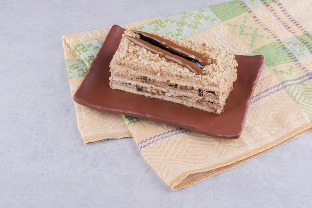 Selbst gemachter kuchen auf braunem teller mit tischdecke.