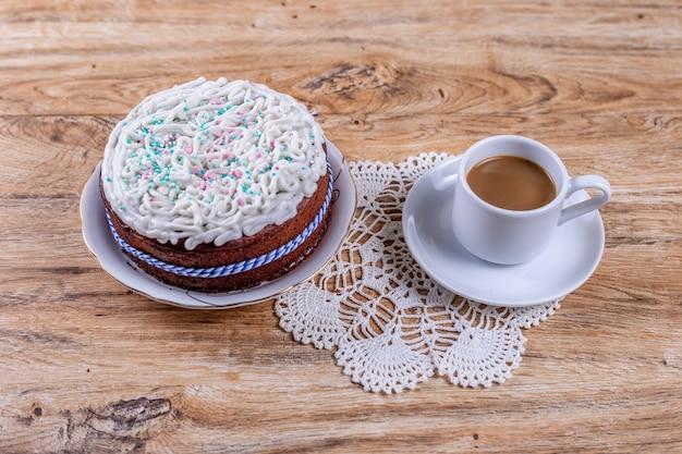 Selbst gemachter kuchen auf einer gehäkelten serviette auf einem holztisch mit einer tasse kaffee