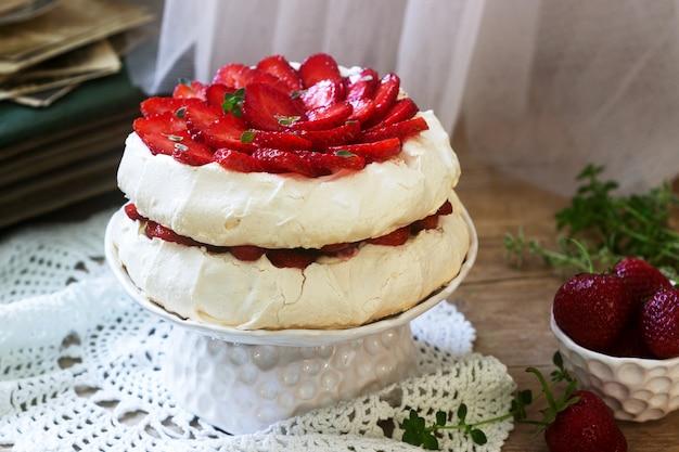 Selbst gemachter kuchen der pavlova-meringe mit erdbeeren und creme