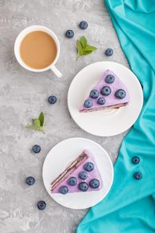 Selbst gemachter kuchen mit auflaufcreme und blaubeermarmelade mit tasse kaffee. ansicht von oben.