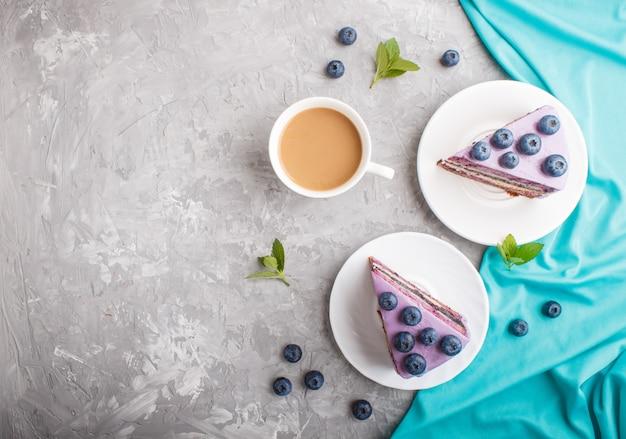 Selbst gemachter kuchen mit auflaufcreme und blaubeermarmelade mit tasse kaffee. draufsicht hintergrund