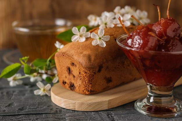 Selbst gemachter kuchen mit den rosinen verziert mit blumen mit apfelmarmelade.