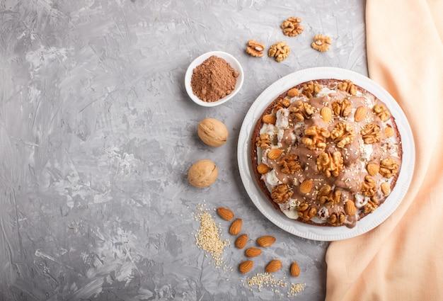 Selbst gemachter kuchen mit milchcreme, kakao, mandel, haselnuss mit orange gewebe. draufsicht, kopie, raum.