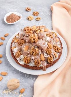 Selbst gemachter kuchen mit milchcreme, kakao, mandel, haselnuss mit orange gewebe, seitenansicht.