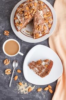 Selbst gemachter kuchen mit milchcreme, kakao, mandel, haselnuss mit orange textil und einem tasse kaffee. draufsicht, kopie, raum.