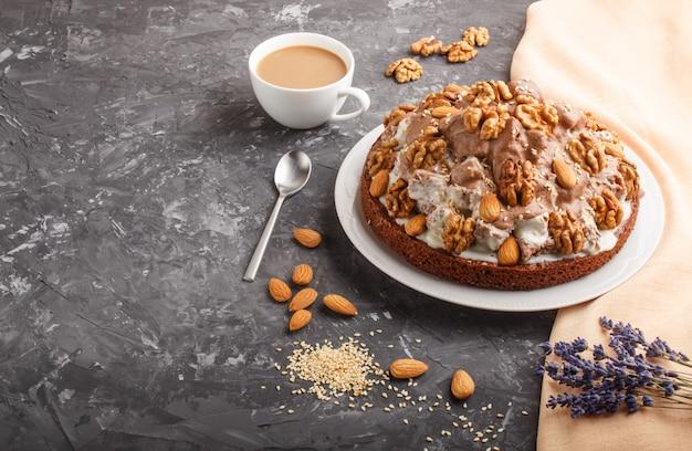 Selbst gemachter kuchen mit milchcreme, kakao, mandel, haselnuss mit orange textil und einem tasse kaffee. seitenansicht.