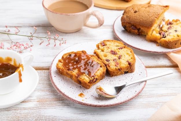 Selbst gemachter kuchen mit rosinen, mandeln, weichem karamell und einer tasse kaffee auf einem weißen hölzernen hintergrund und einem orangefarbenen leinentextil. seitenansicht, nahaufnahme.