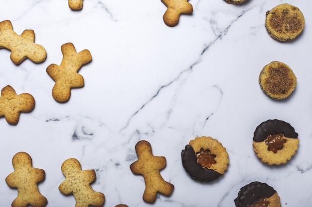 Selbst gemachter lebkuchen, zimt und schokoladenplätzchen auf marmorhintergrund von oben. flach liegen