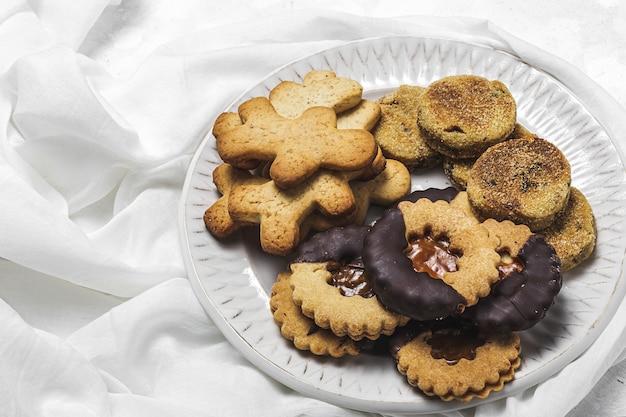 Selbst gemachter lebkuchen, zimt und schokoladenplätzchen auf weißem hintergrund von oben. flach liegen